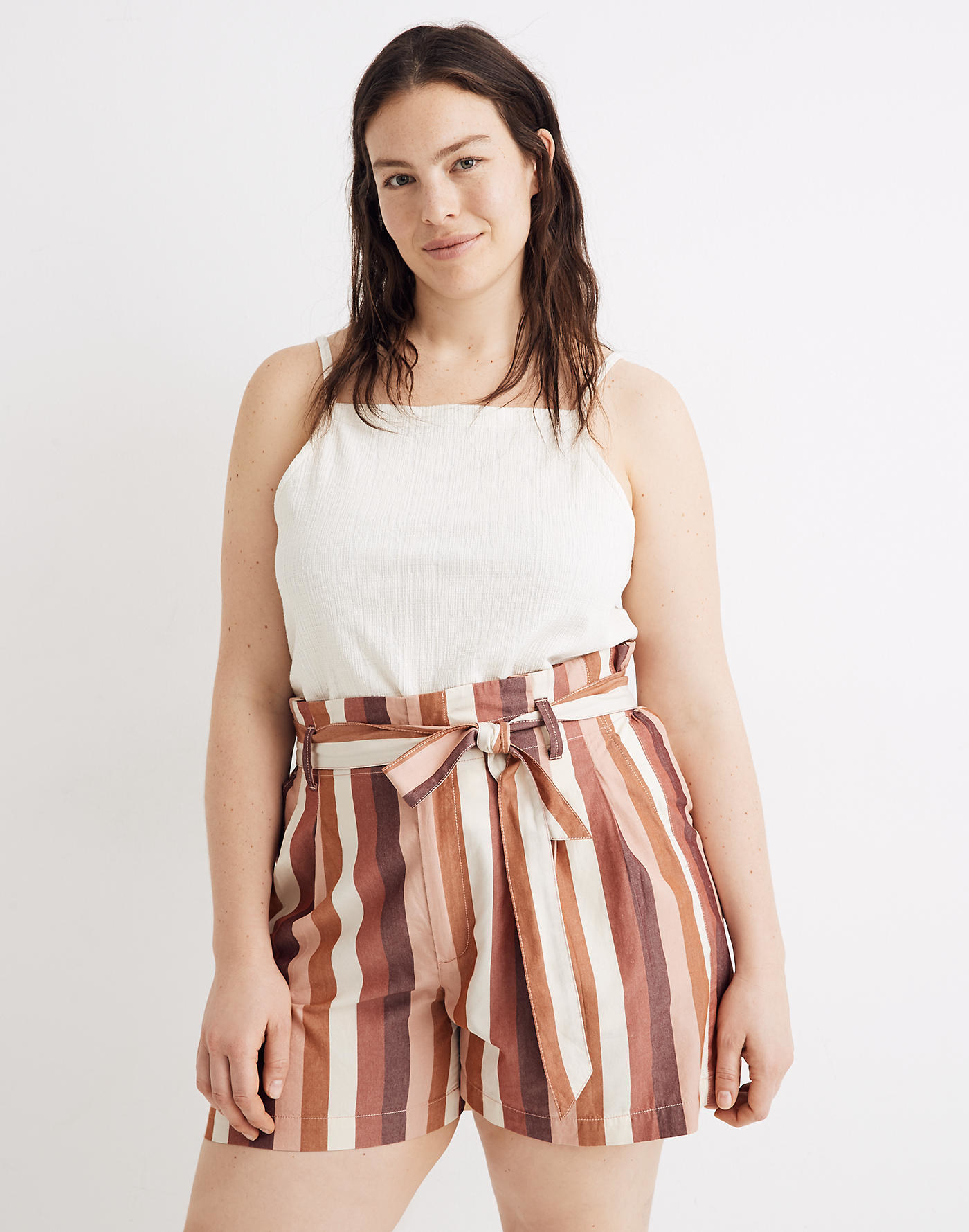 Model wearing the shorts with a tie waist and vertical stripes in white and shakes of pink and orange