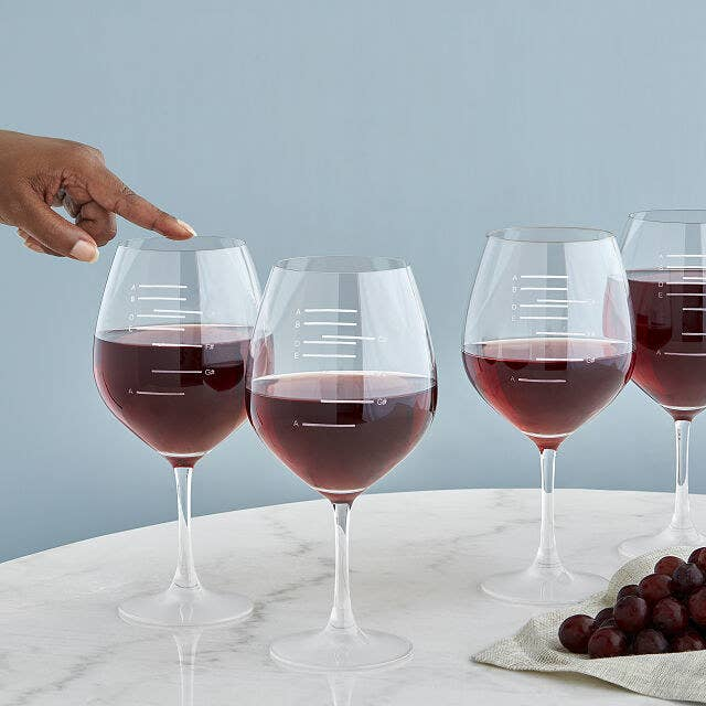 Four musical wine glasses filled to different notated major scales and a finger running along the rim of one of them