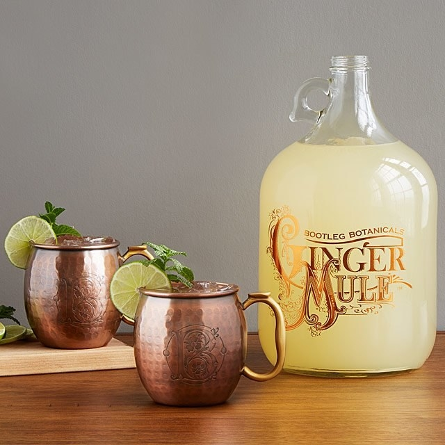 Two Moscow Mule copper mugs next to a bottle of ginger beer