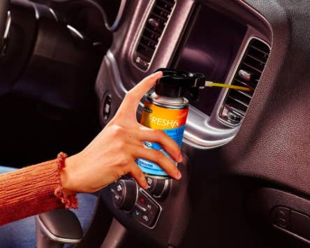 Hand sprays can of Armor All Car Air Freshener and Cleaner to clean vents inside a black vehicle
