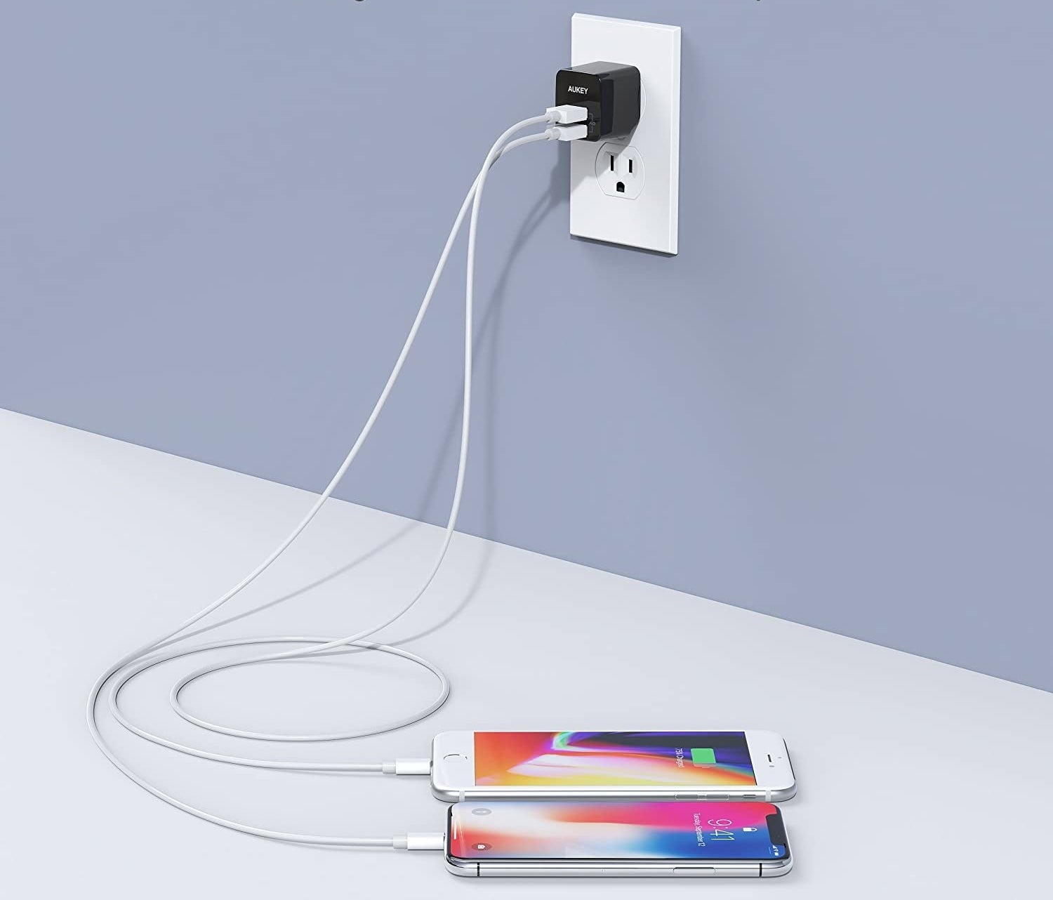 A charger plugged into the wall charging two phones