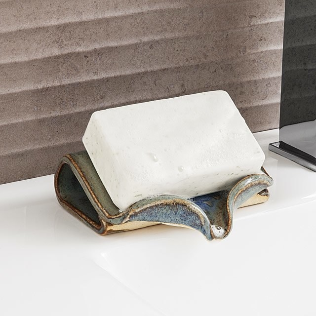 A wet bar of soap perched on a ceramic self-draining soap dish