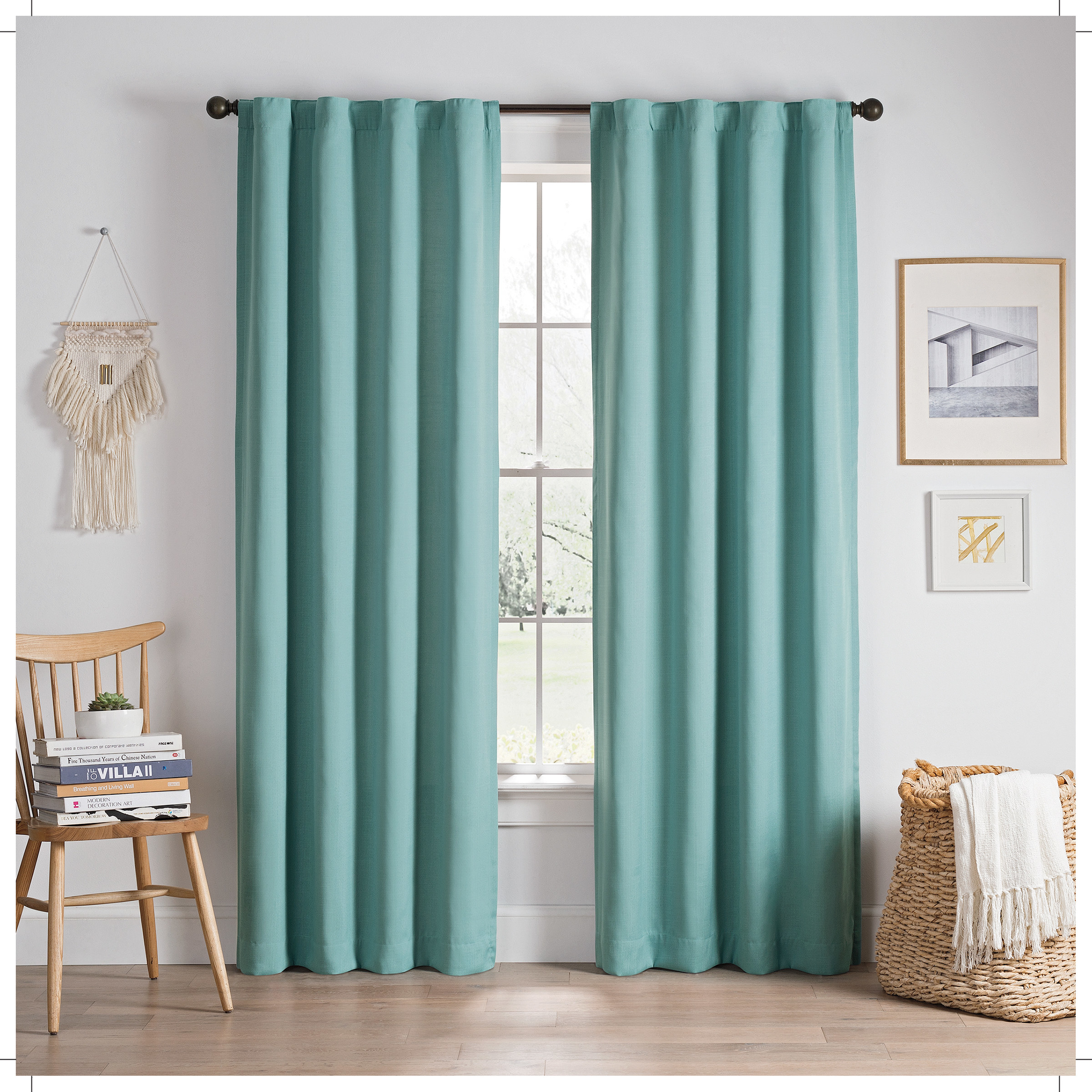 An aqua color set of curtains hanging around a window
