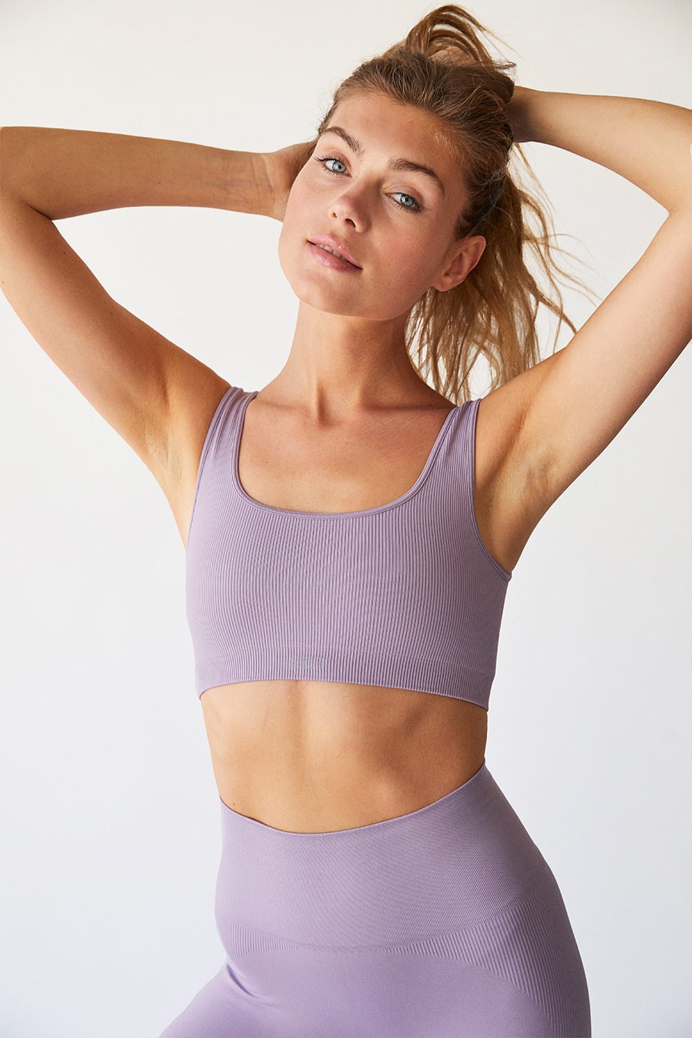 a model in a purple ribbed sports bra with thick straps