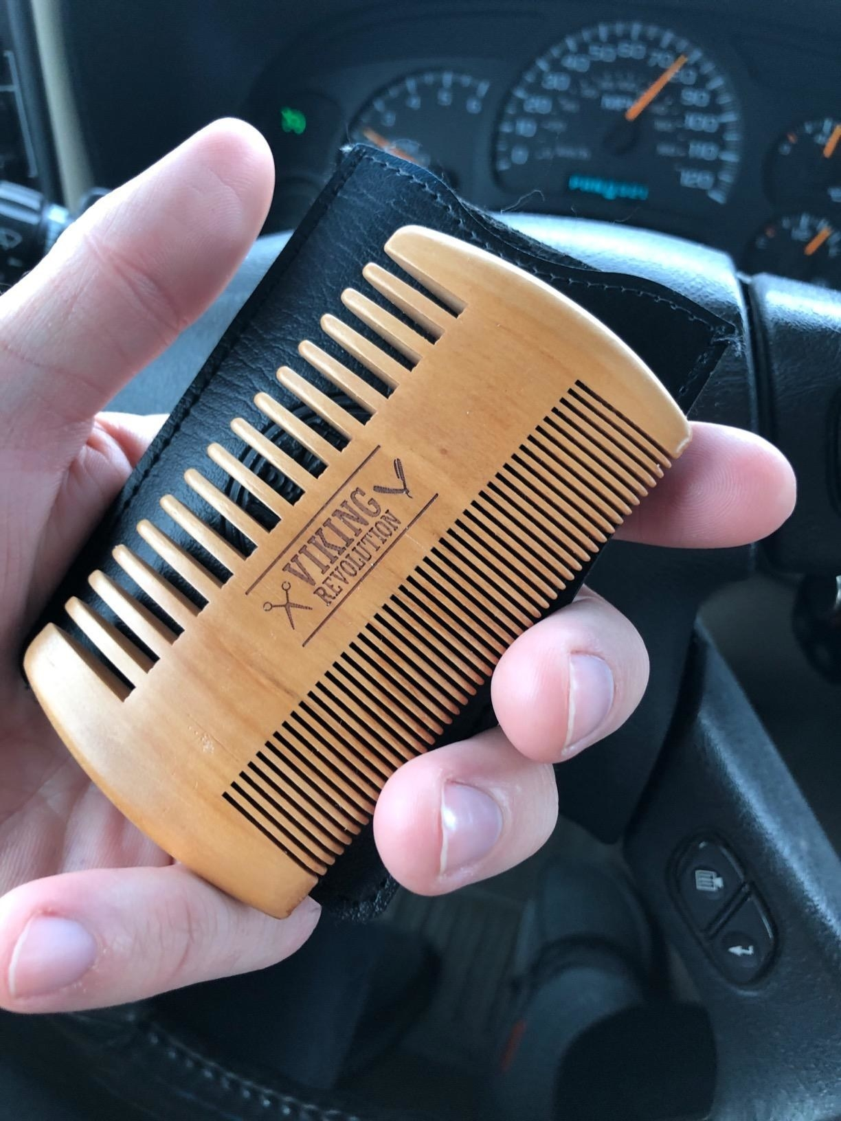 A reviewer's hand holding a light brown wooden comb and a black leather carrying case