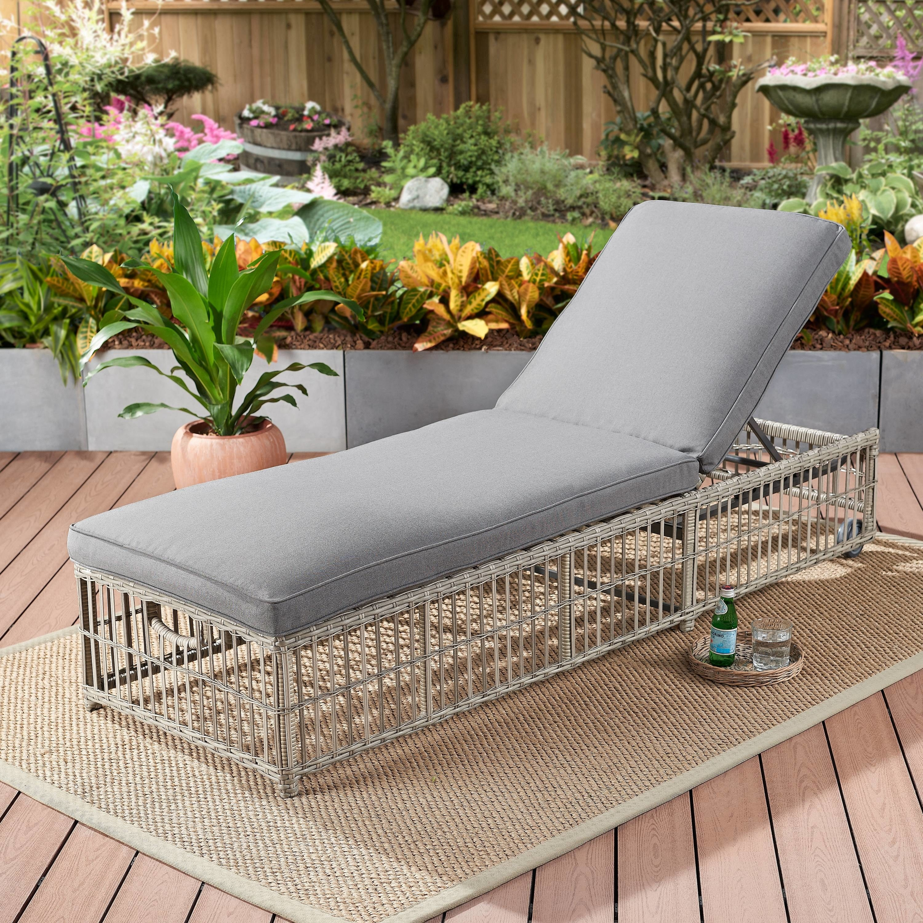 A gray cushioned lounge chair on wicker platform