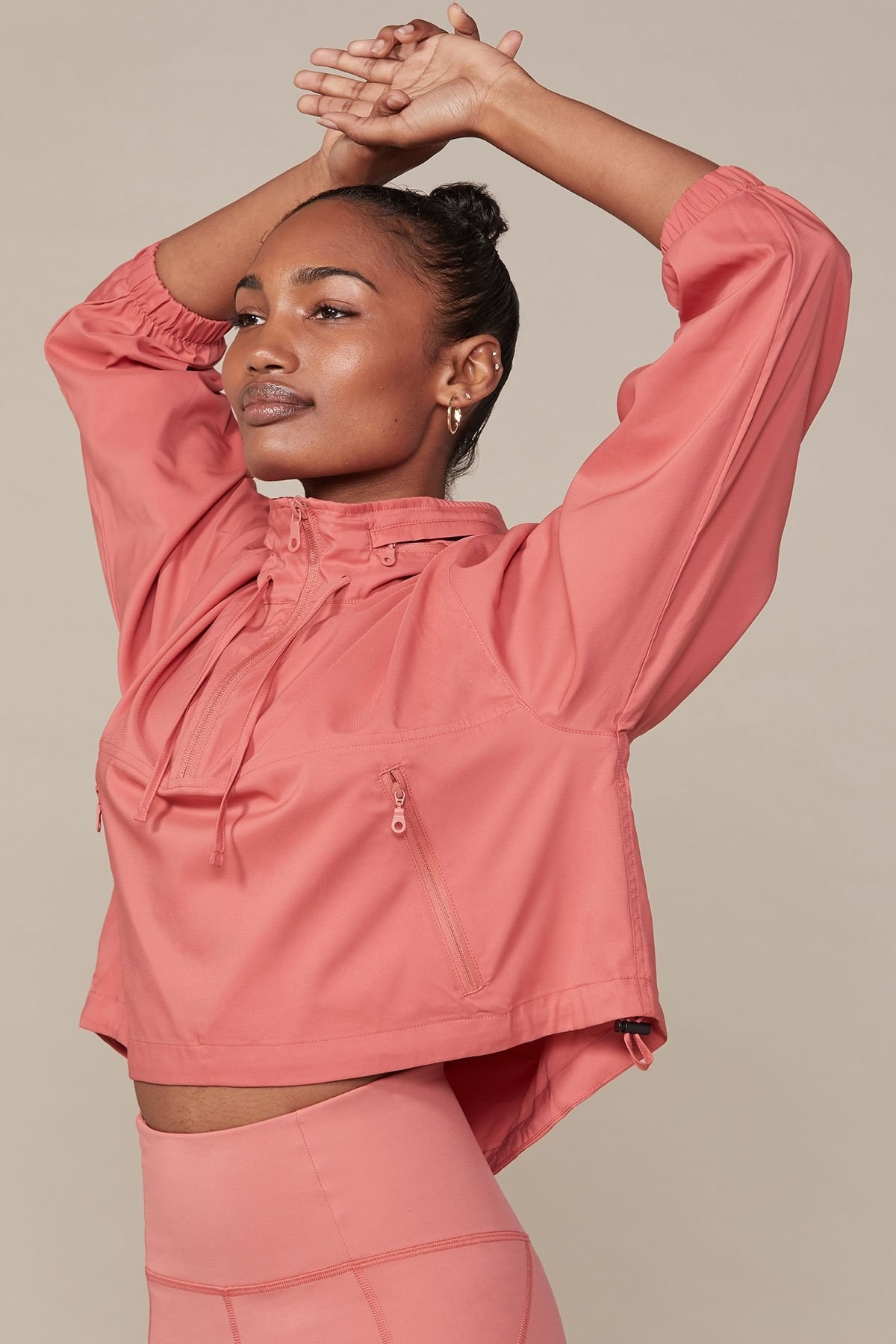 a model wearing a coral color boxy windbreaker with zipper pockets