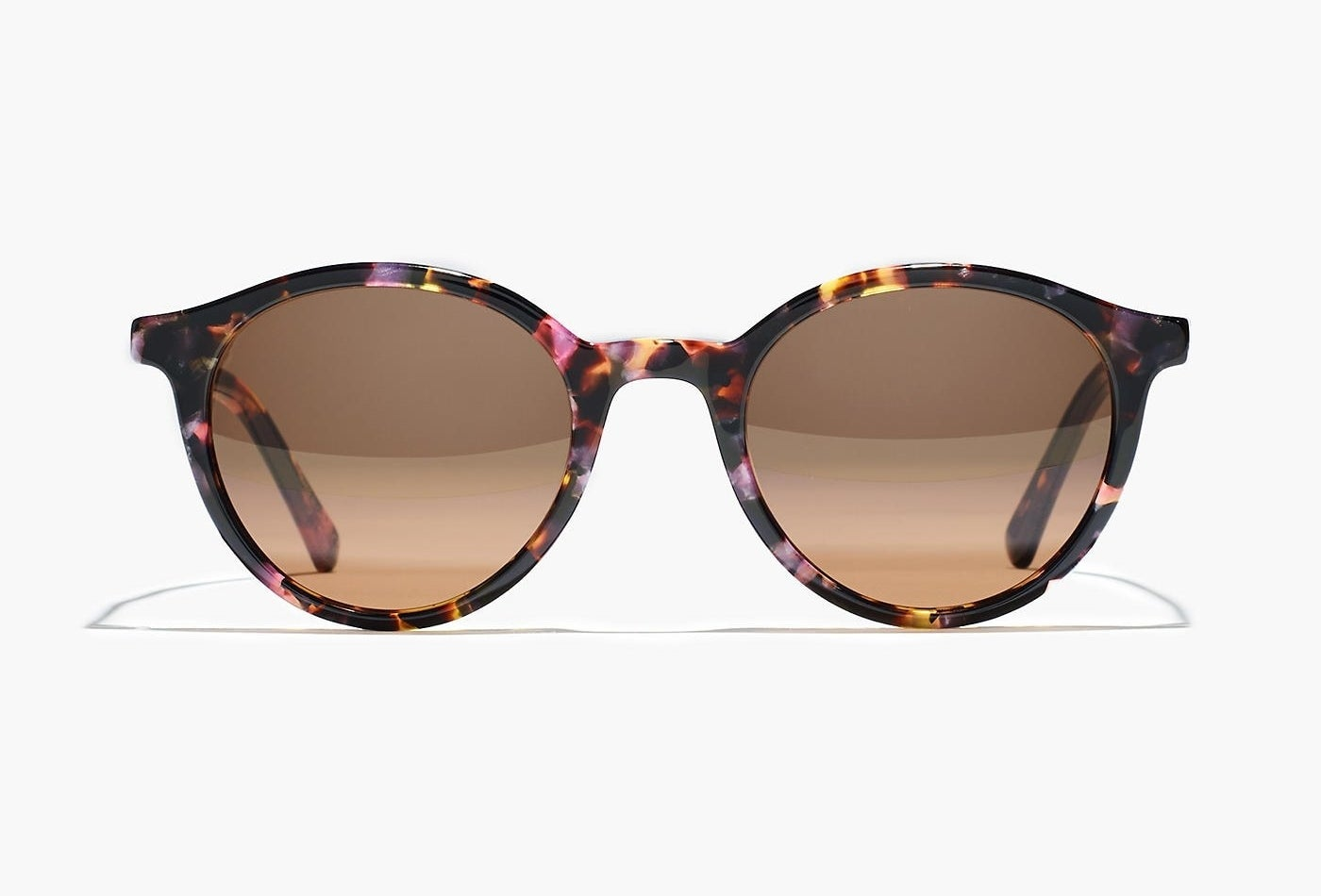 The rounded sunglasses with pink, purple, and brown tortoise-shell and brown lenses