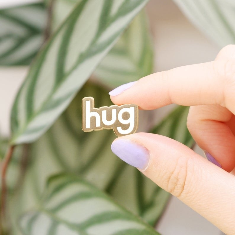"Fingers holding the pin, which reads ""hug"" in white and gold block letters"