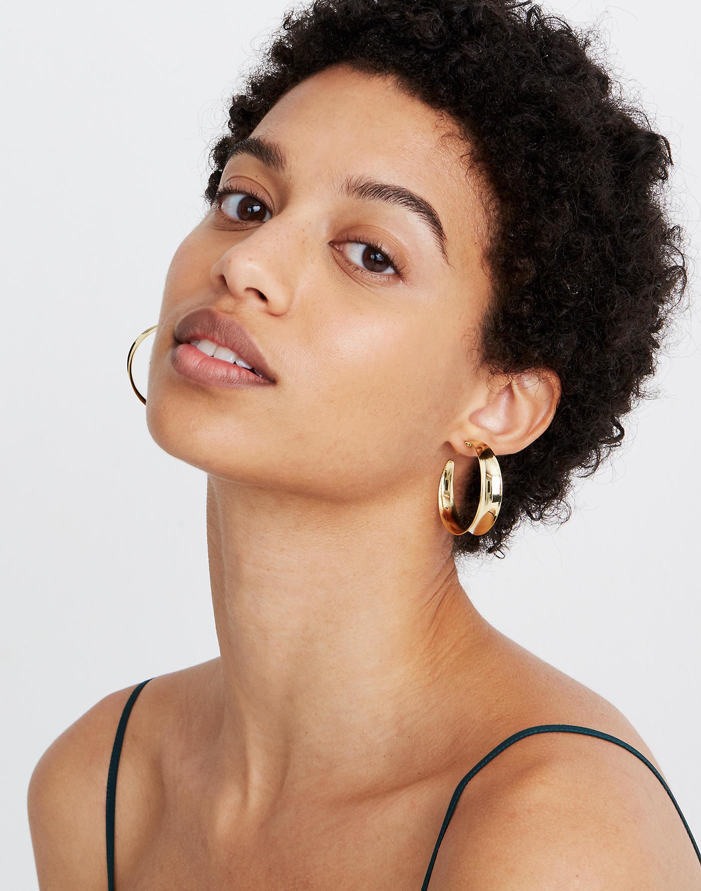 Model wearing the oversized sculptural earrings in gold