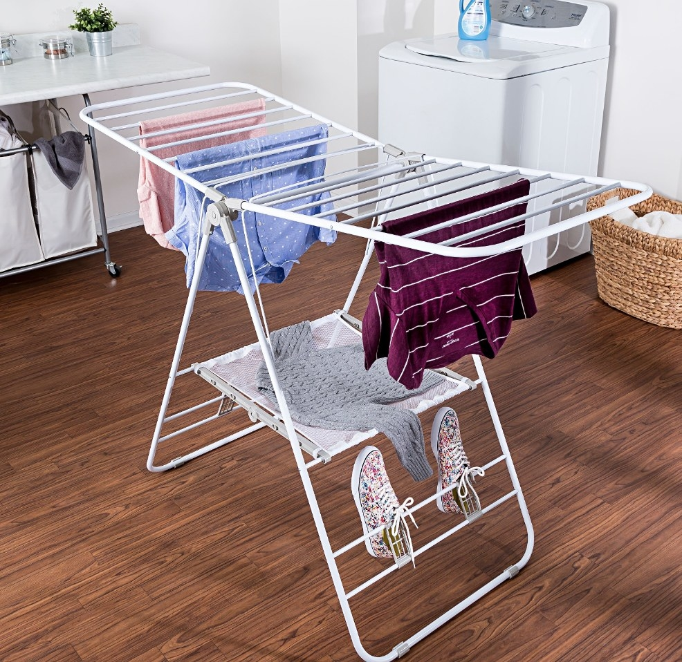a white fold out laundry drying rack