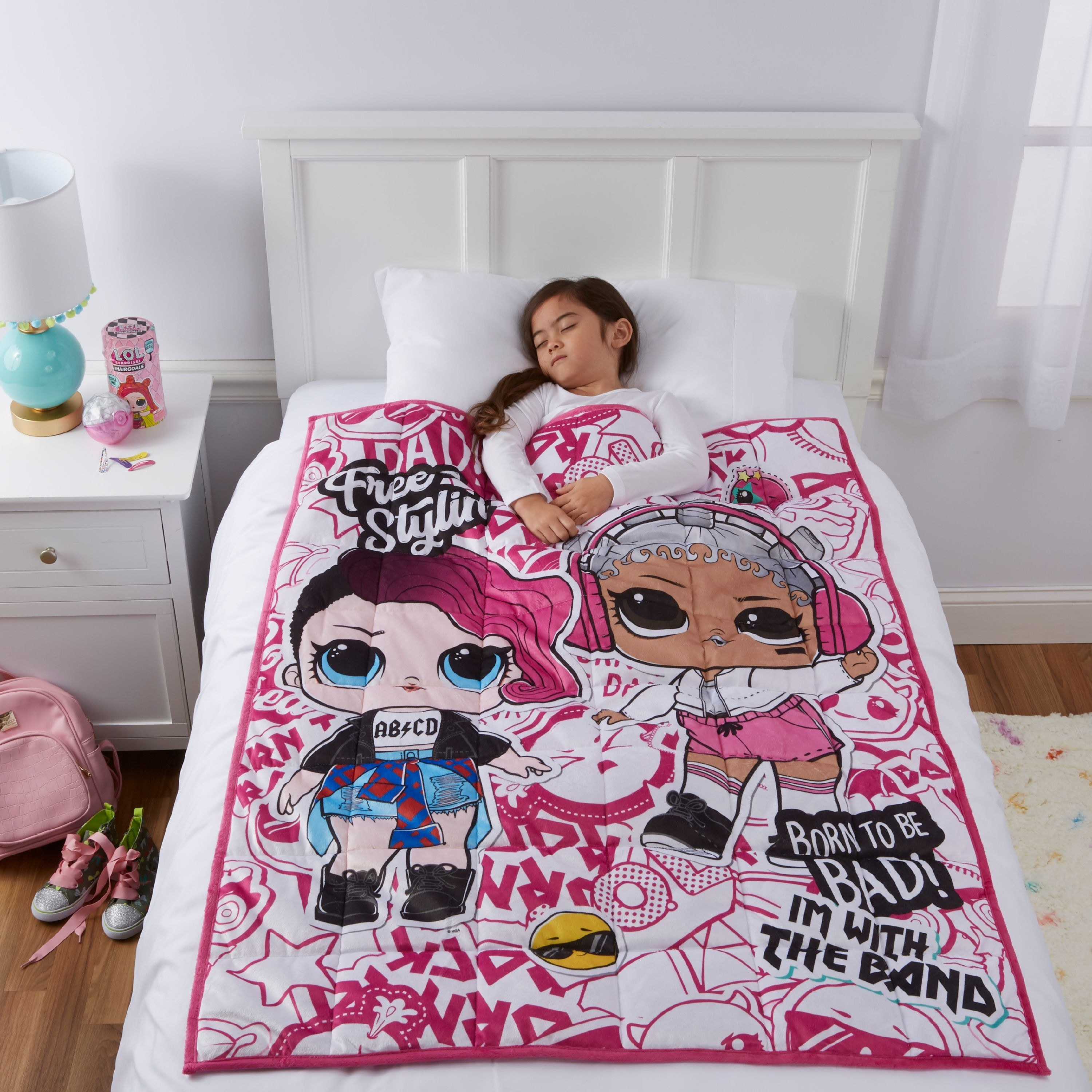 A pink blanket on a twin bed