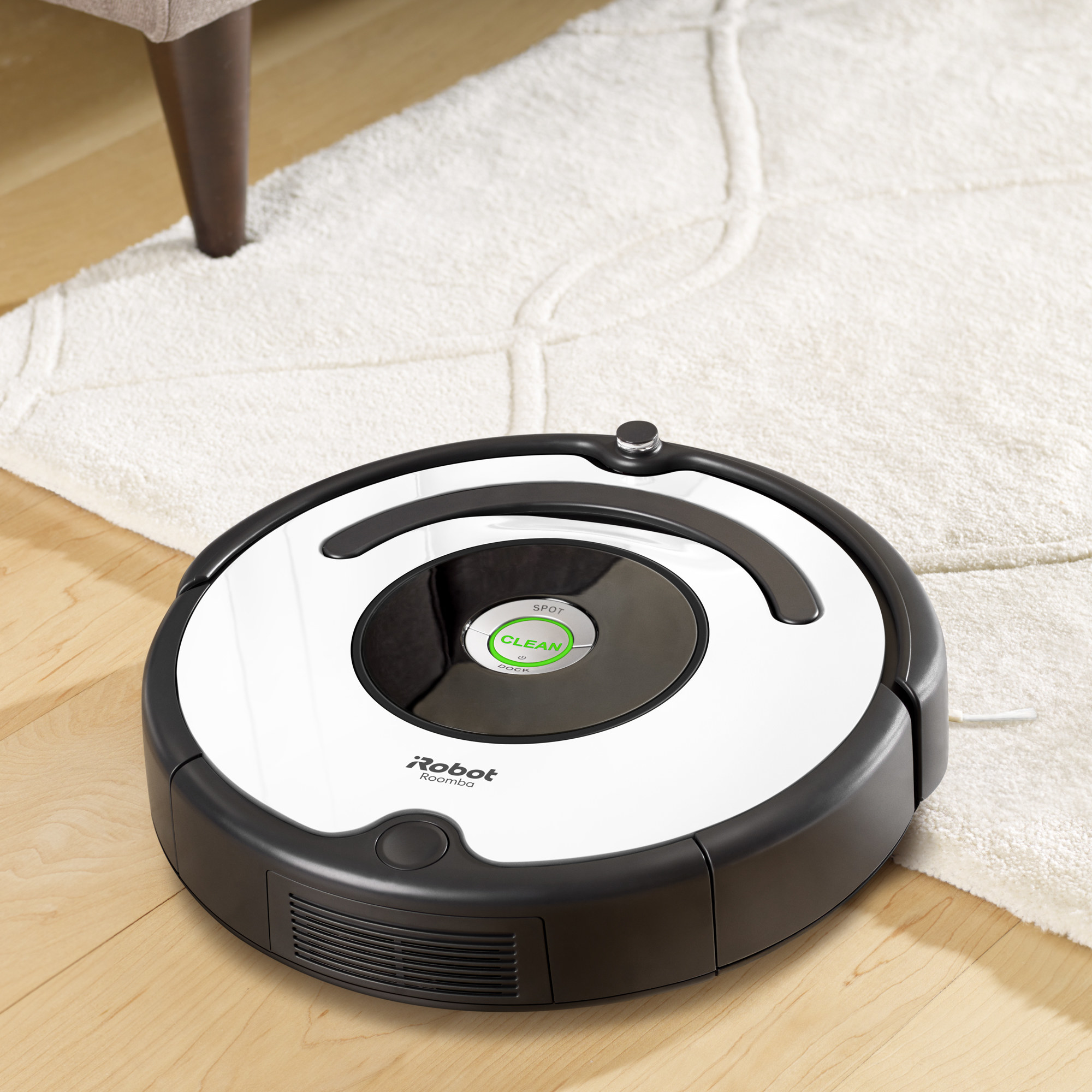 A black and white roomba on a carpet and hardwood floor