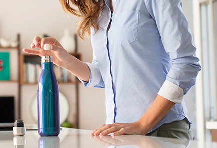 Model drops a Bottle Bright Cleaning Tablet into a blue iridescent water bottle