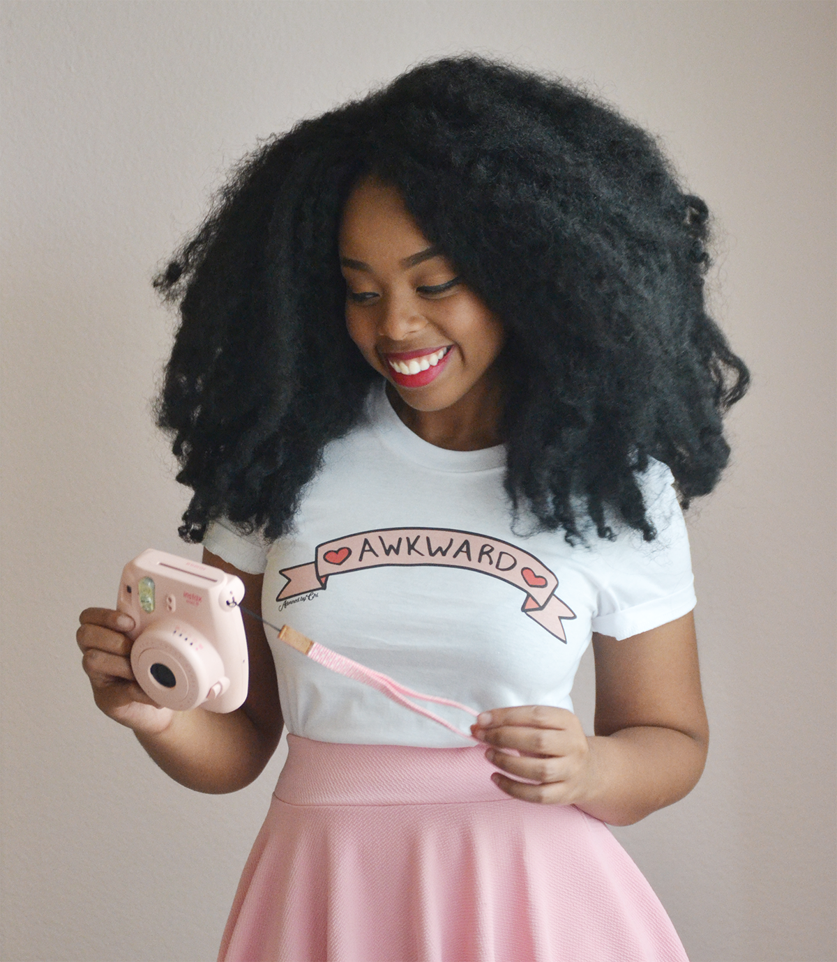 "A model wearing the white tee printed with a pink banner that reads ""AWKWARD"" with hearts on either side"