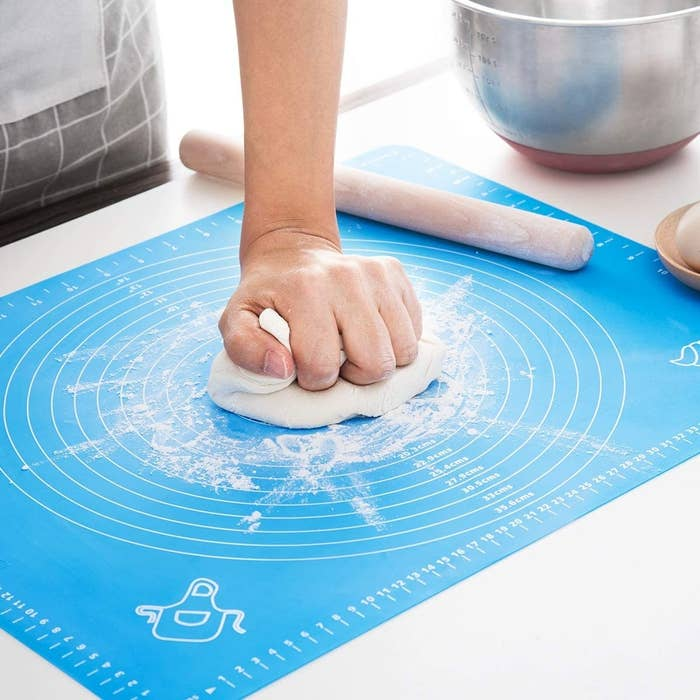 A person smashes a ball of dough onto the centre of the silicone baking mat