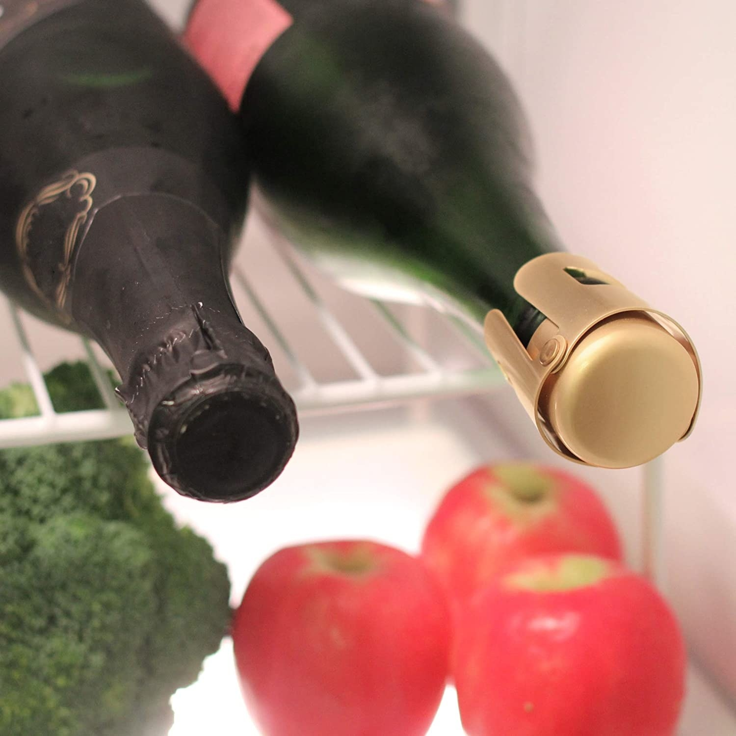 A bottle of sparkling wine capped with the bottle stopper rests on a fridge shelf