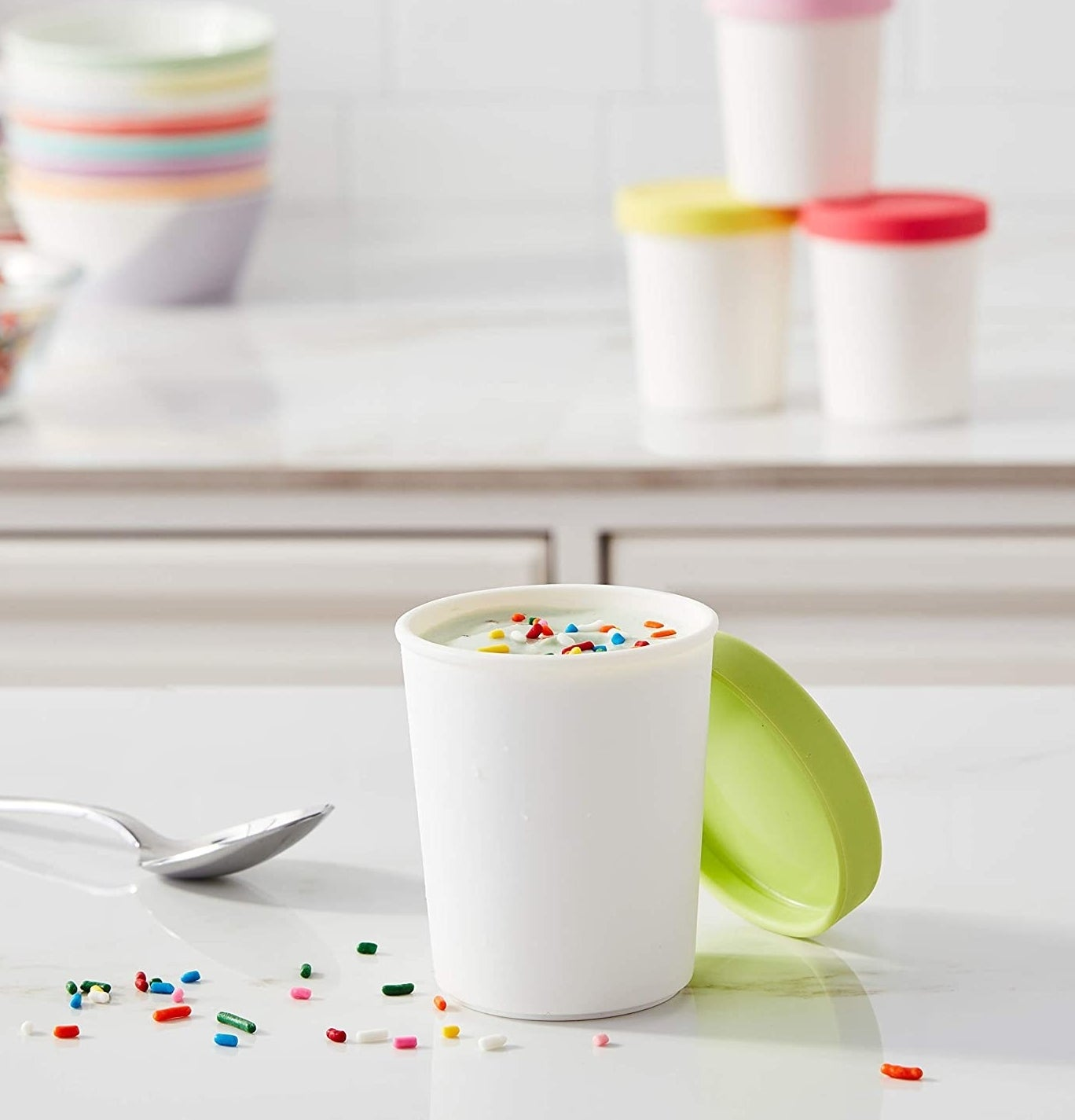A mini ice cream tub full of vanilla ice cream sits on a countertop with scattered sprinkles around it