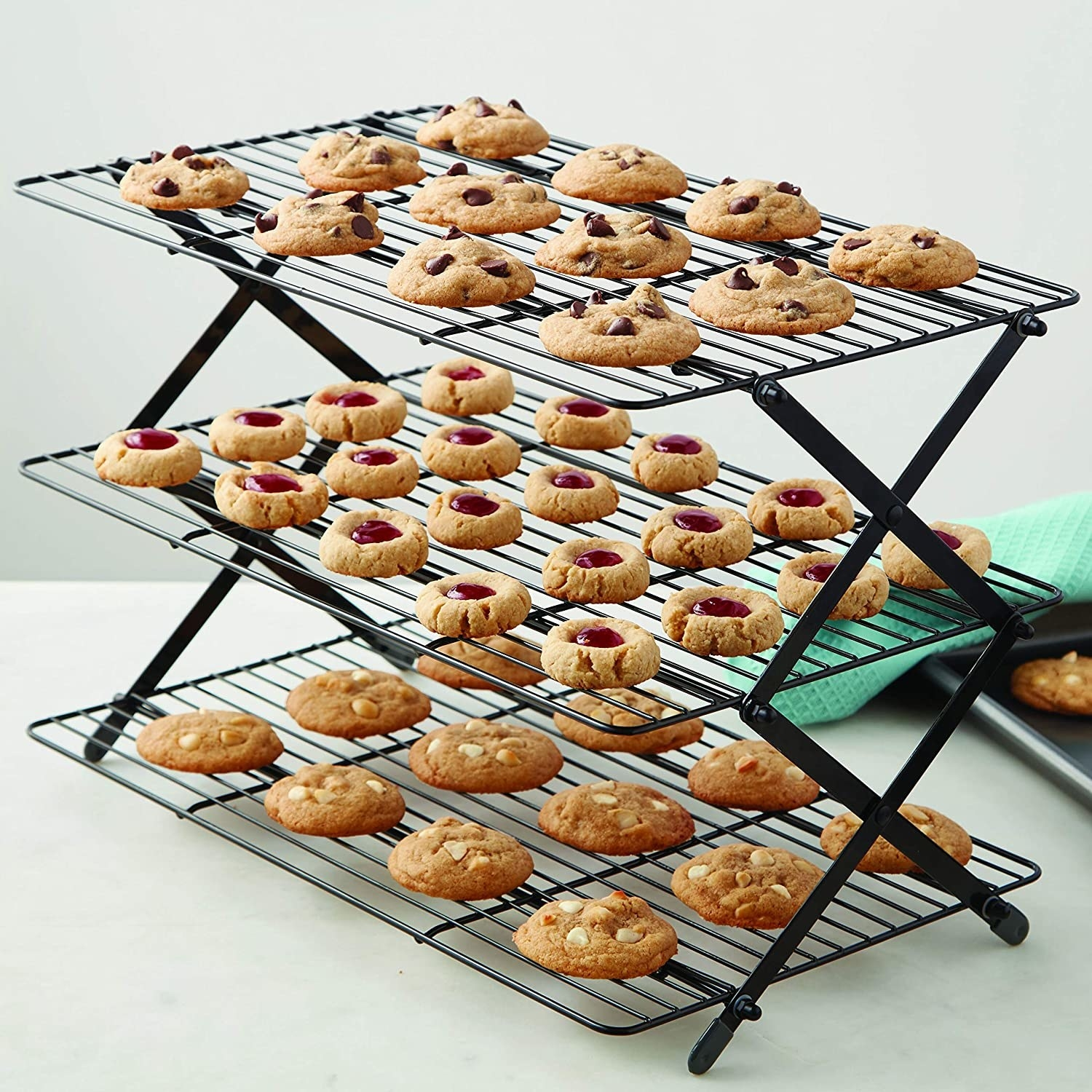 A three tier cookie rack stands on a counter top full of different cookies