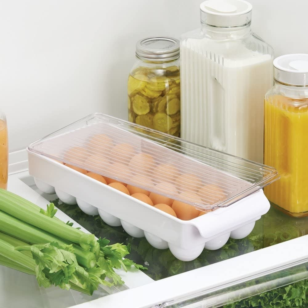 The egg organizer rests on a fridge shelf where fresh brown eggs are visible inside