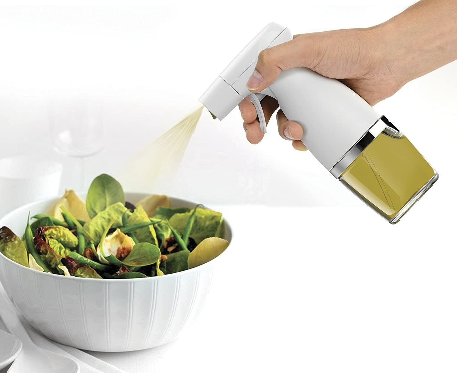 A person uses the mister to spritz a salad with olive oil