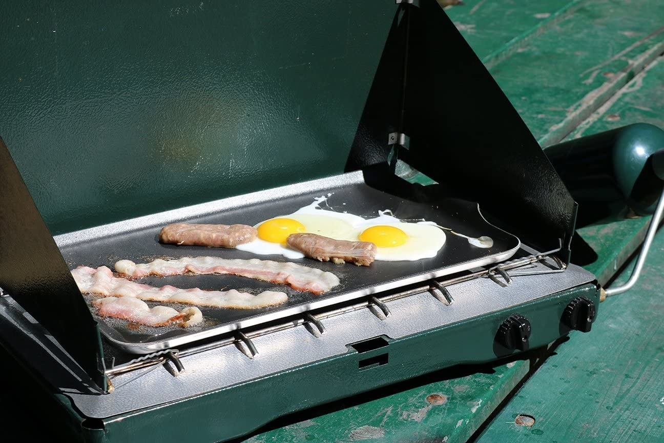 A portable burner with a griddle on top with eggs and bacon