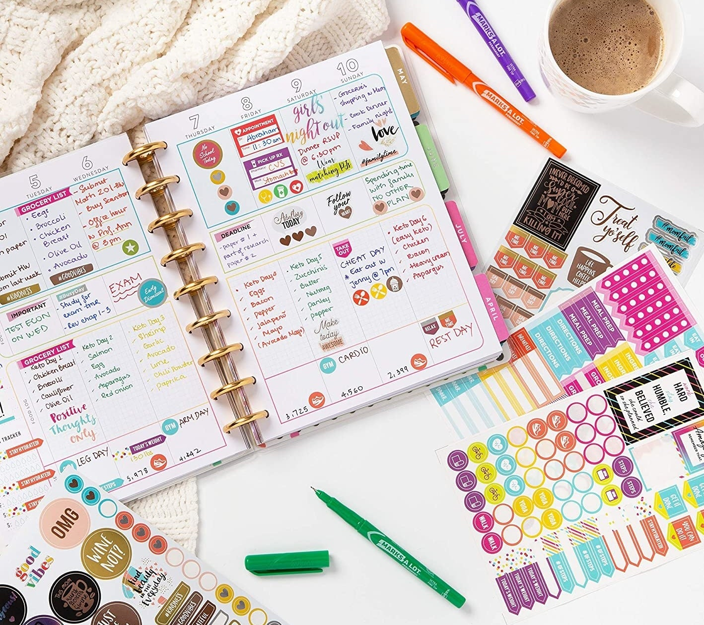 An agenda covered in planner stickers with extra sheets of planner stickers next to it