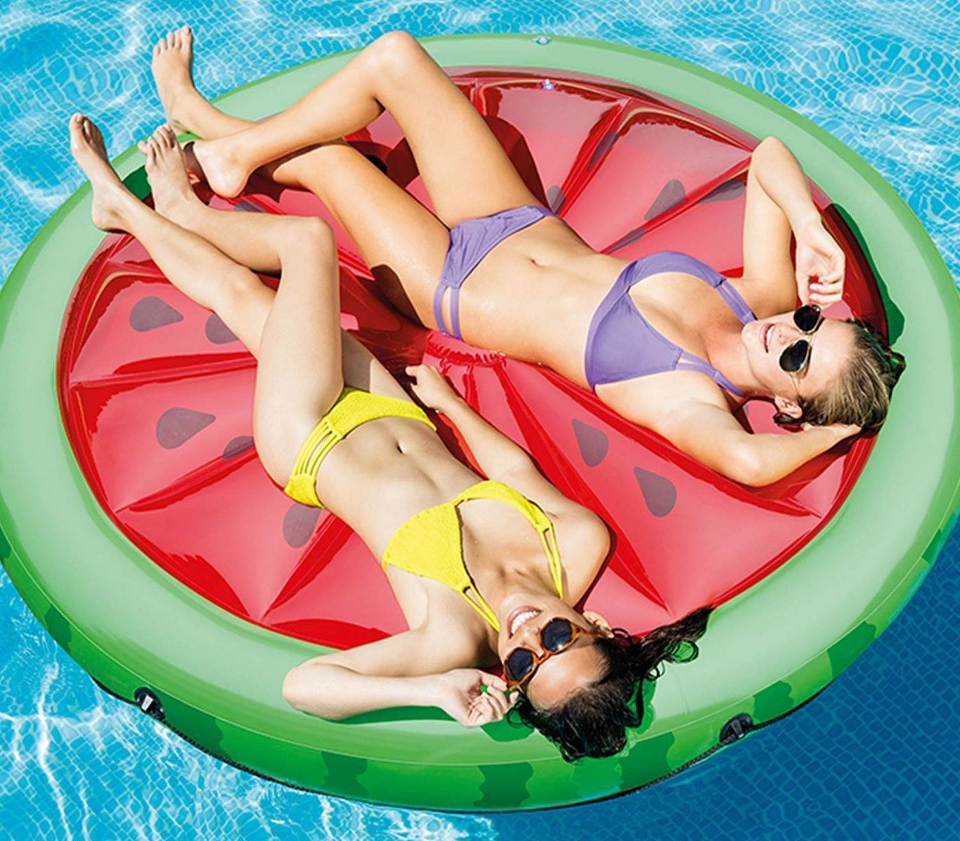 Two models lounging on a green and red water melon pool float