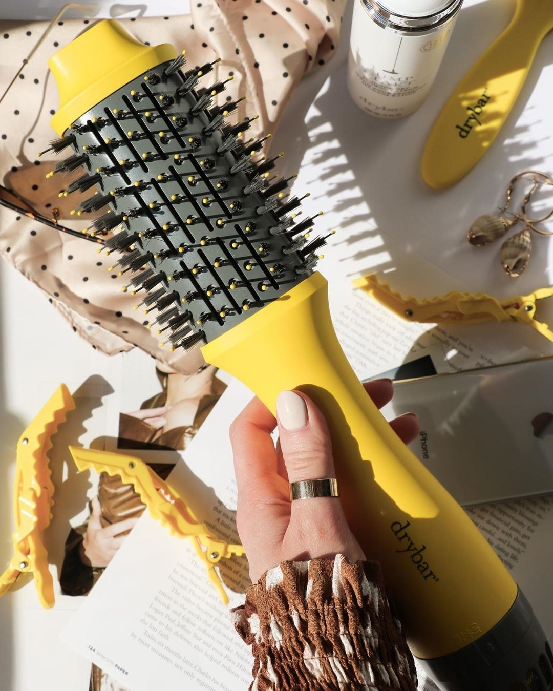 A hand holds the elliptical cylinder hot air brush. It's a bit flatter than a pure cylindrical round brush. The bristles are nylon and tufted