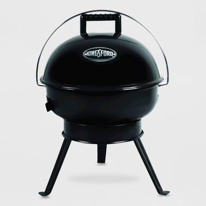 A shiny black three-leg charcoal grill