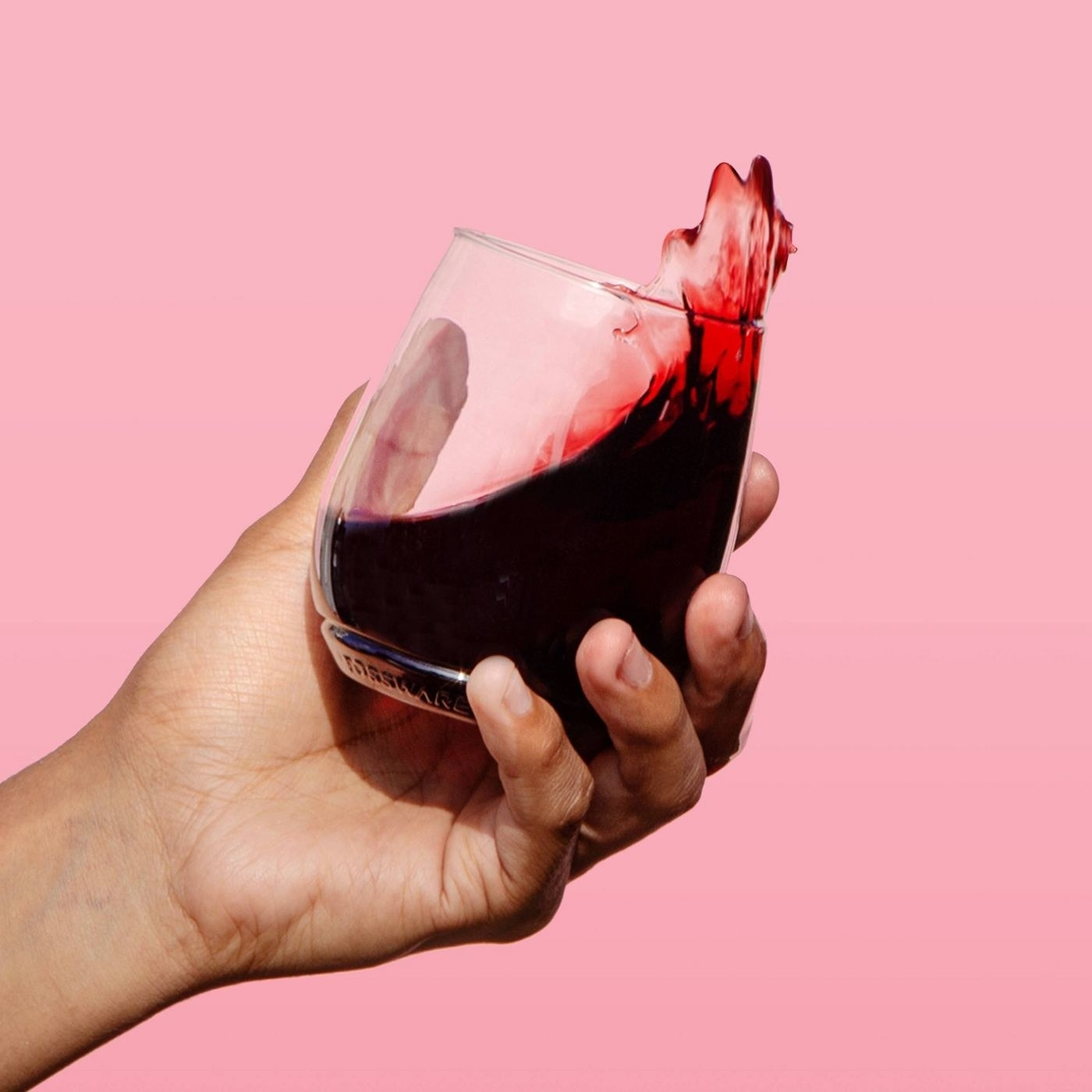 A model's hand swishing some wine in a stemless glass