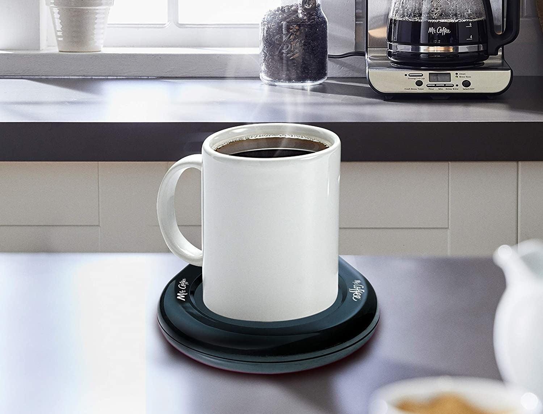 A device keeps a mug of coffee warm on a table