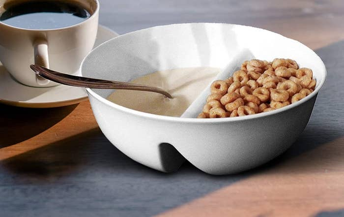 A bowl with milk in one compartment and cereal in another