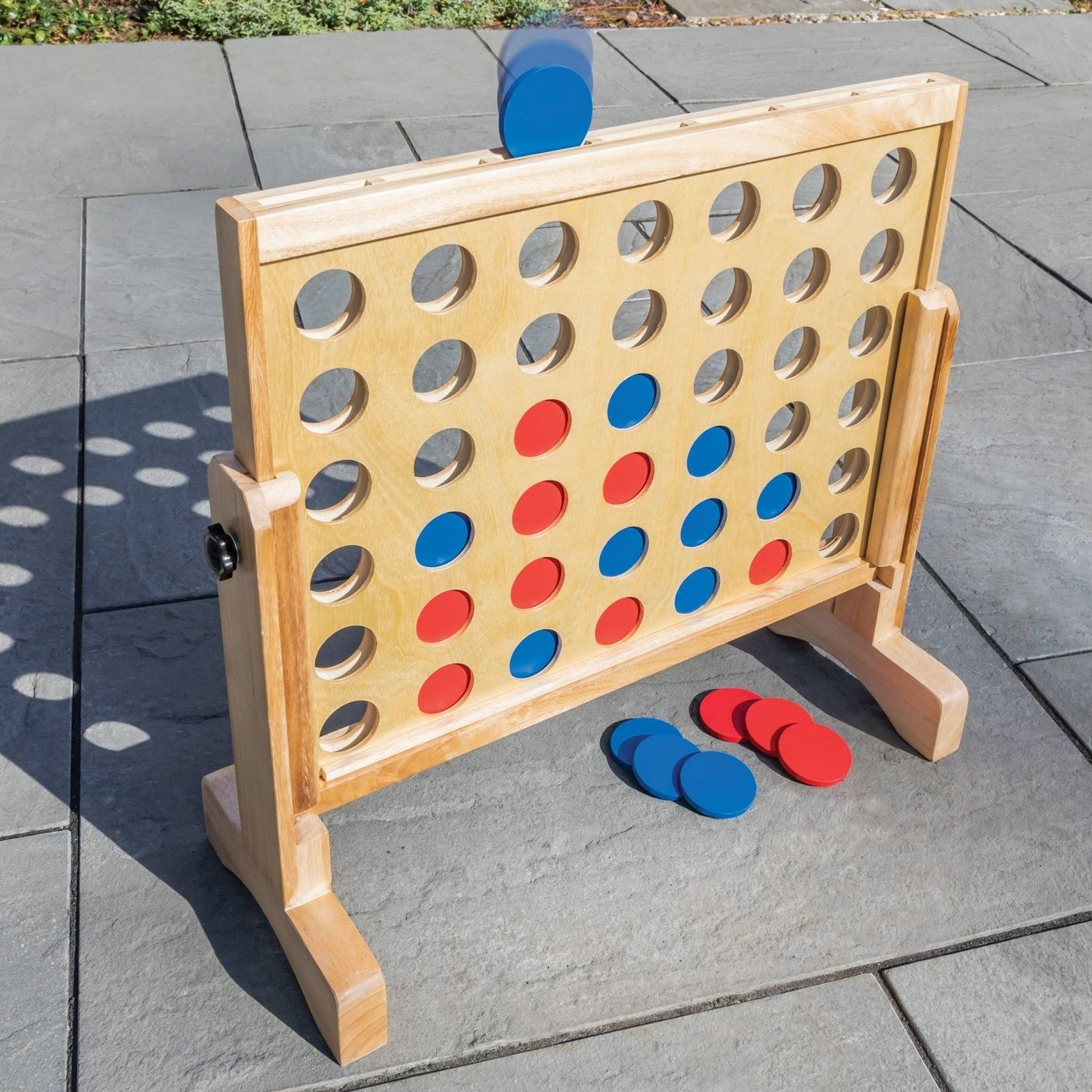 A large wooden connect four board with blue and red discs