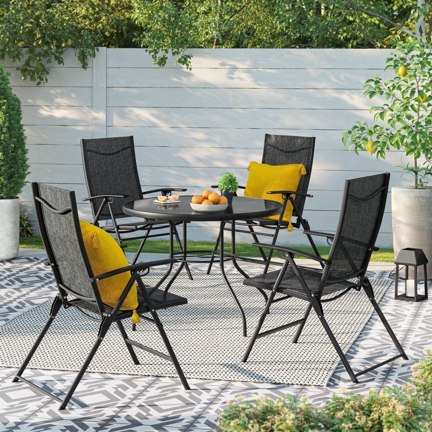 A round black table with four black folding chairs and two yellow pillows