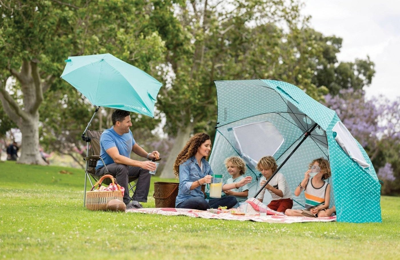 A family sitting under a large teal umbrella