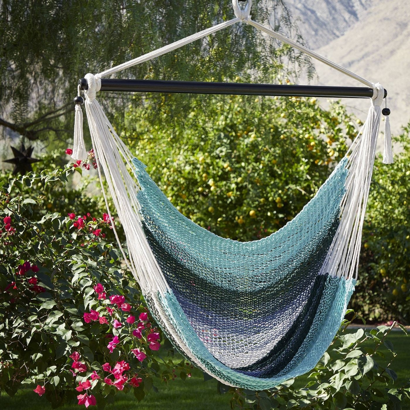 A hanging hammock chair in blue, white, and seafoam green
