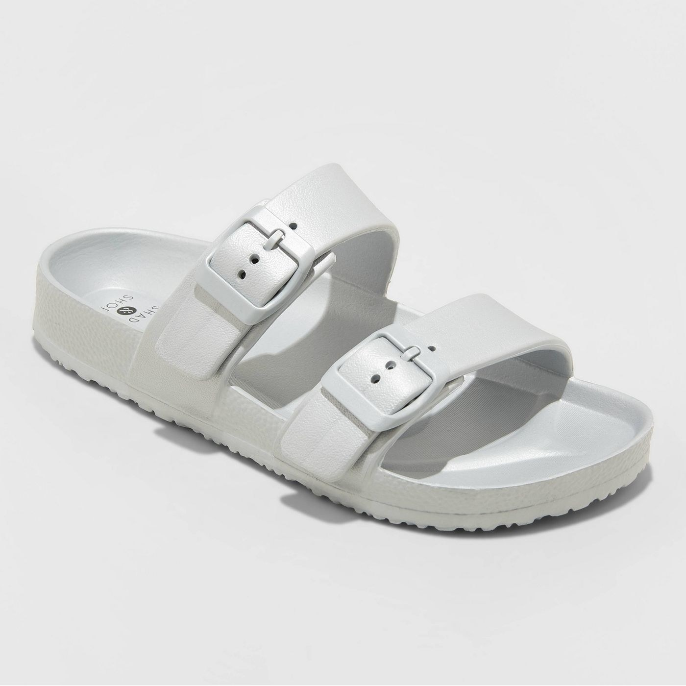 A white sandal with two buckled straps