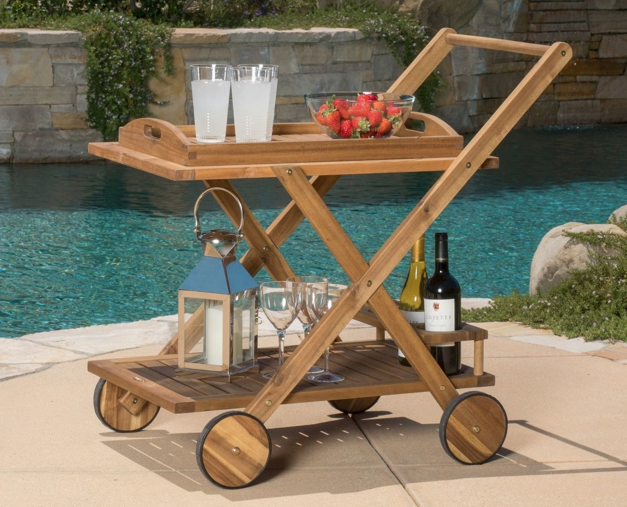 Two-level bar cart on four wheels holding wine, glasses, and a bowl of fruit