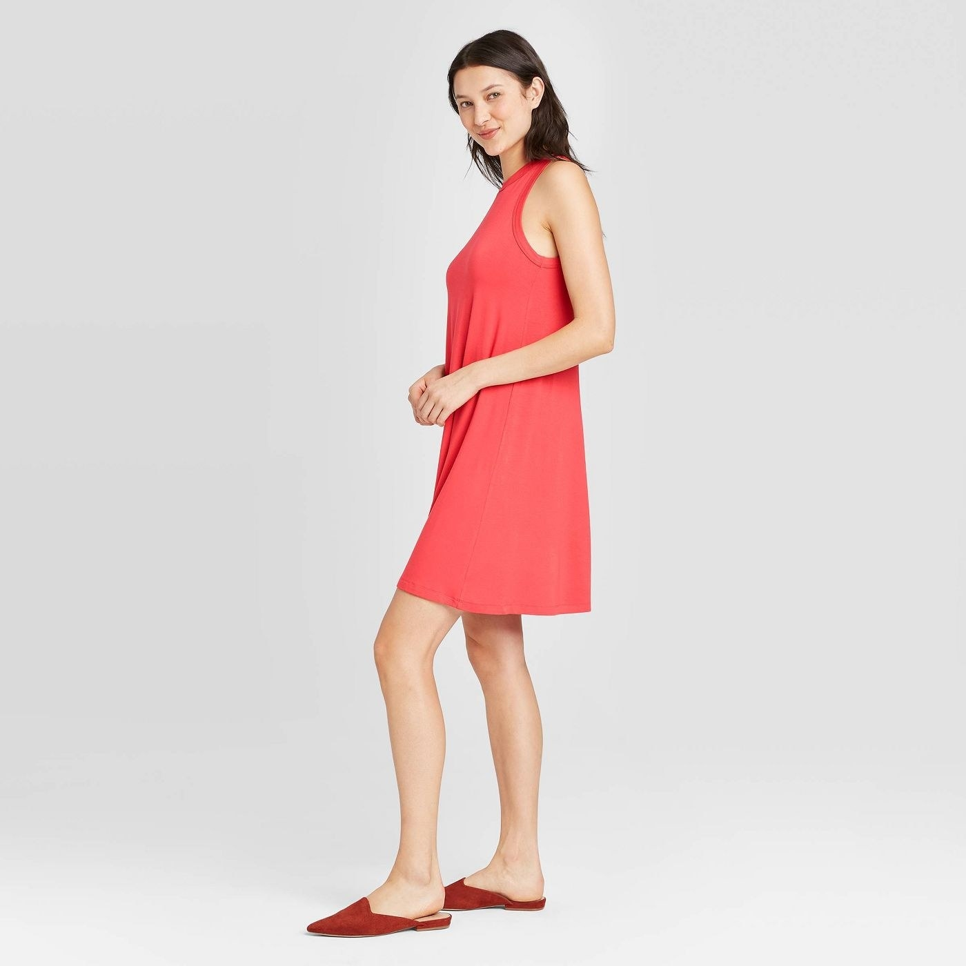 Model wearing a light red dress that hits above the knee