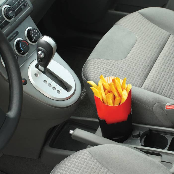 A french fry holder plugged into the cup holder of a car with fries in it