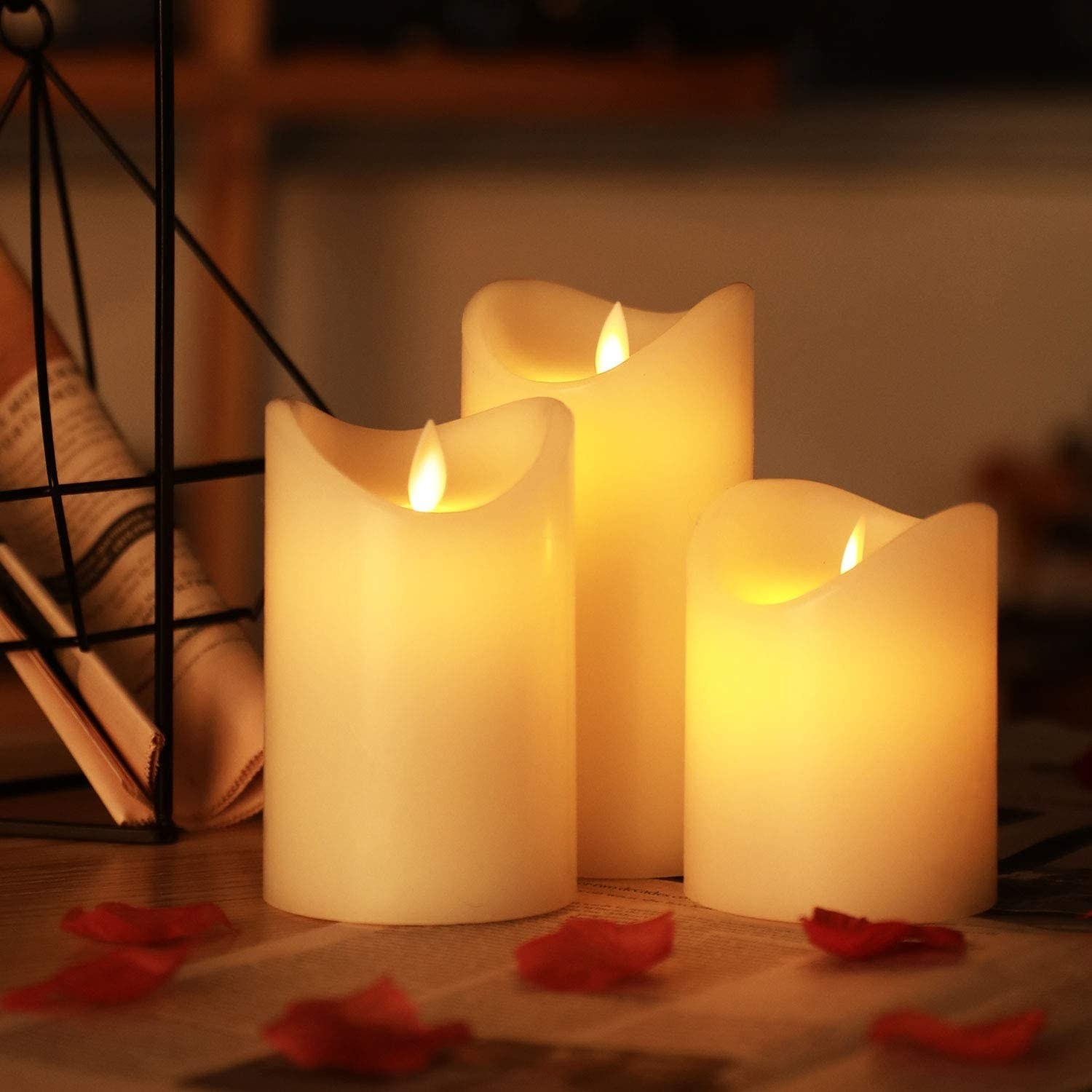 Three flameless candles surrounded by rose petals