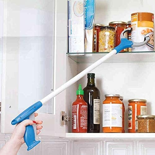 person holding the long grip with a claw at the end reaching for cans in a food cabinet
