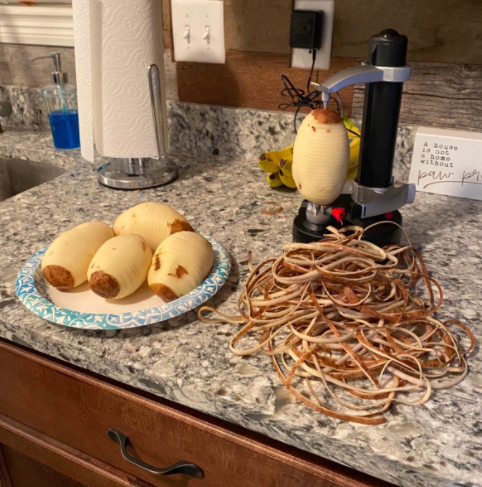 reviewer pic of potato peeler in use with stack of peels on kitchen countertop beside a plate of four peeled potatoes
