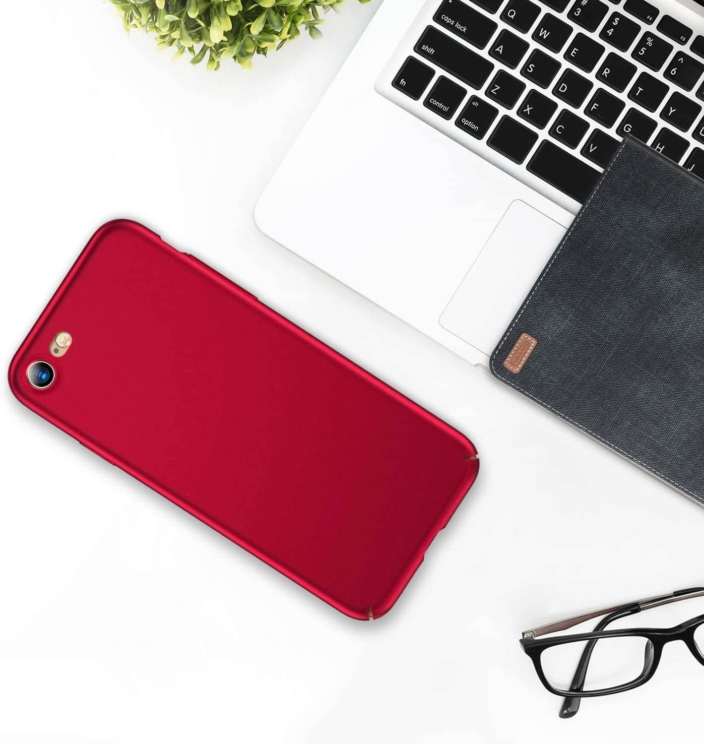 A phone with the case on lying next to a laptop on a desk