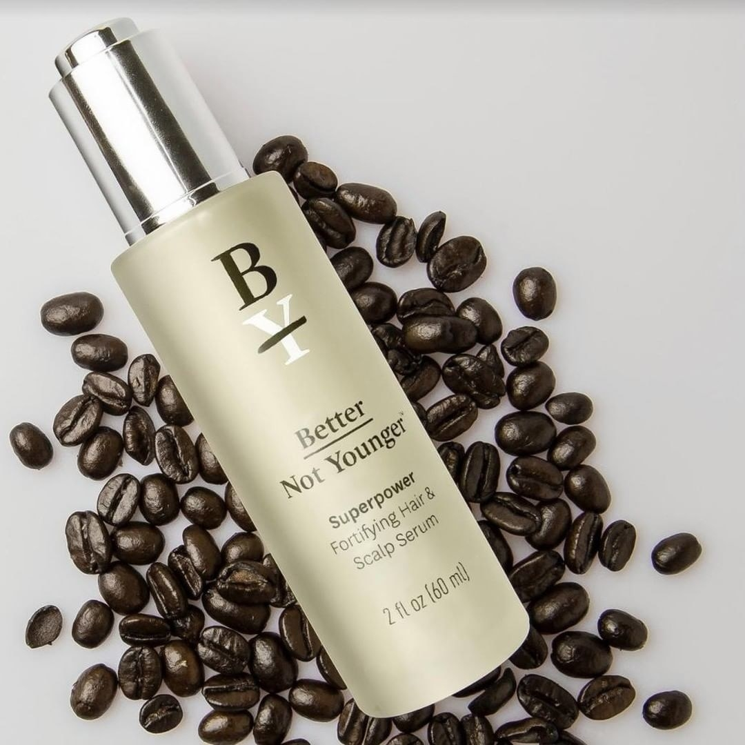 A bottle of the Better Not Younger hair and scalp serum lying on coffee beans