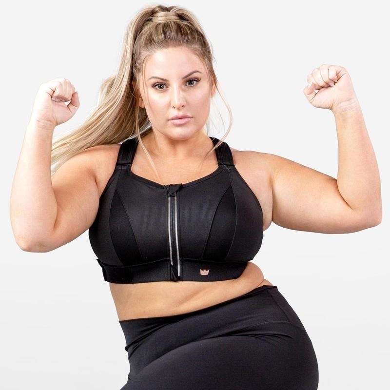 Model wearing the sports bra in black with thick straps, a wide band around the chest and a zipper down the front