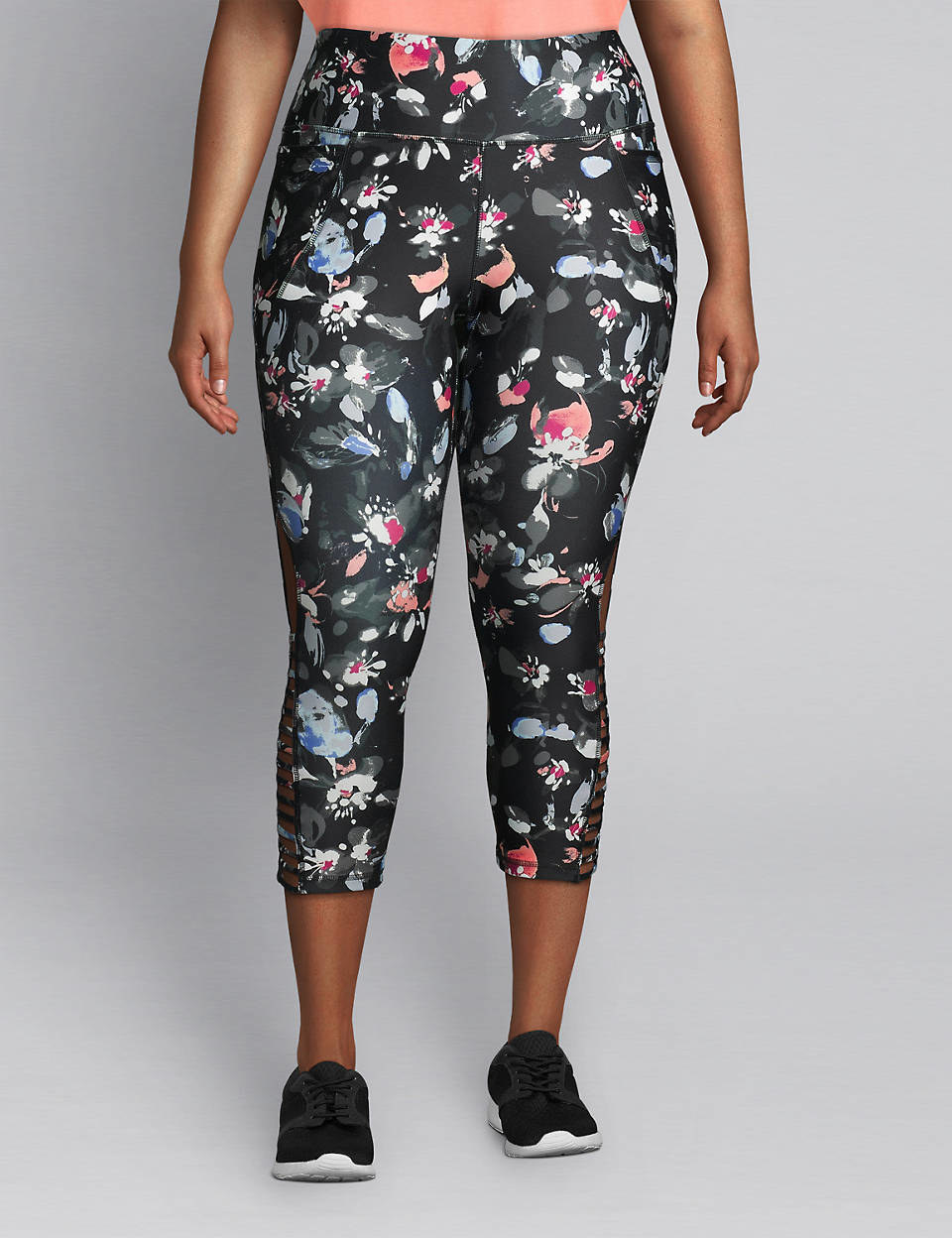 The capri legging with a wide waistband and strappy ladder detailing on the bottom side in black with a white, pink, blue, and grey floral print all over it