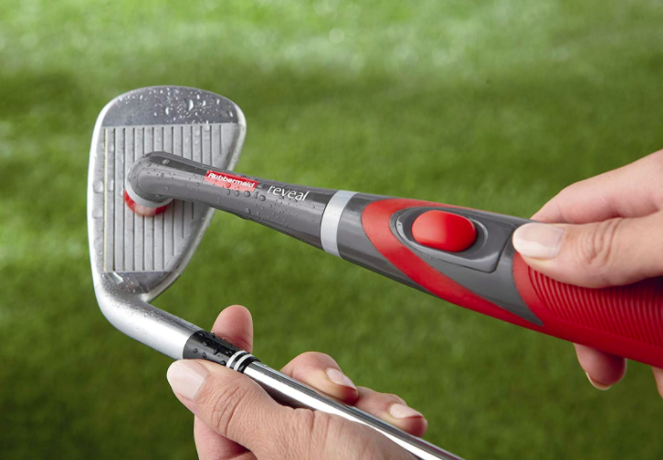 Hand holds red mini power scrubber while cleaning the front part of a golf club