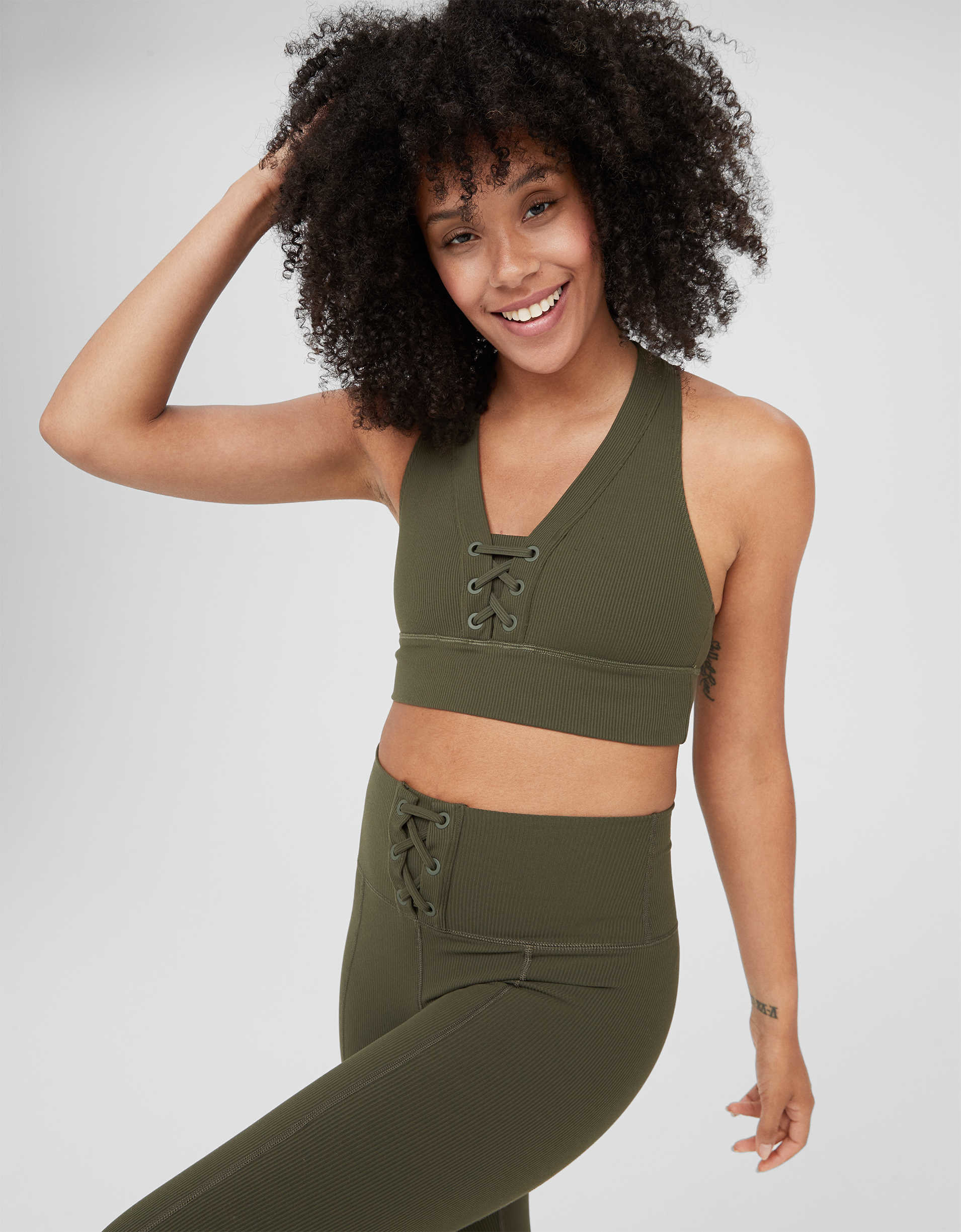 Model wearing the sports bra with thick straps, thick band around the chest, and a lace-up front by the neckline in green